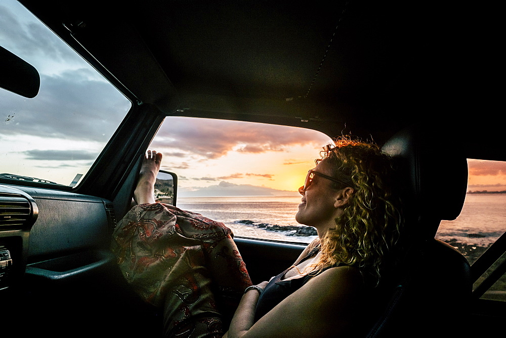 Woman in car with her legs raised watching sunset
