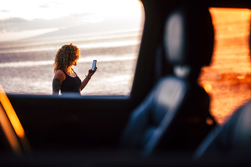 Woman using smart phone behind car window at sunset