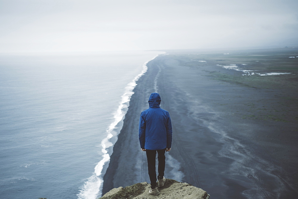 Man wearing blue coat above beach in Vik, Iceland