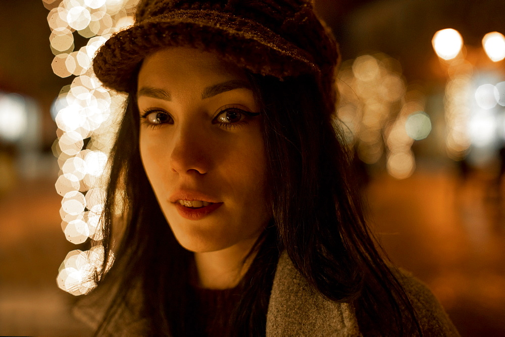 Portrait of young woman wearing woolly hat at night