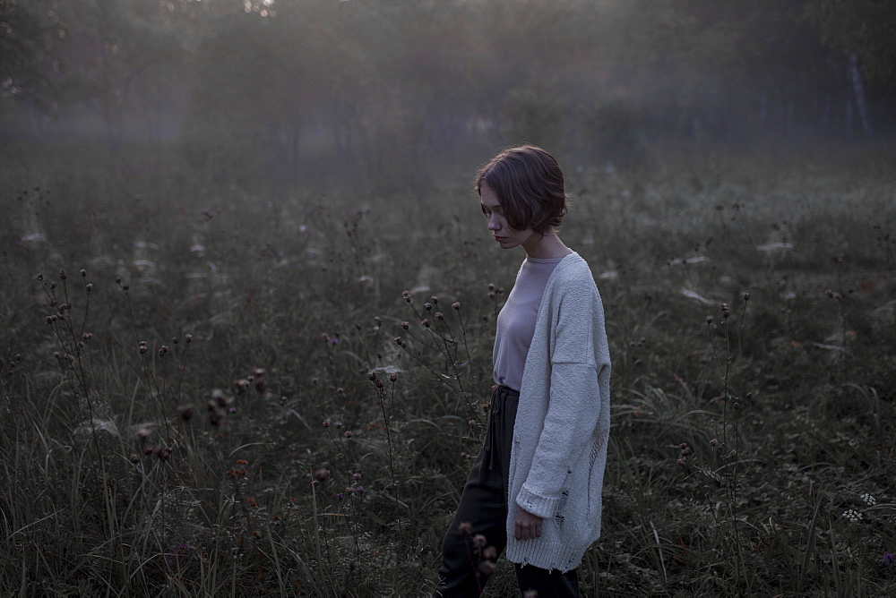 Young woman wearing white cardigan in field at sunset