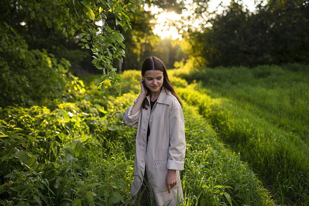 Teenage girl wearing gray coat in field at sunset
