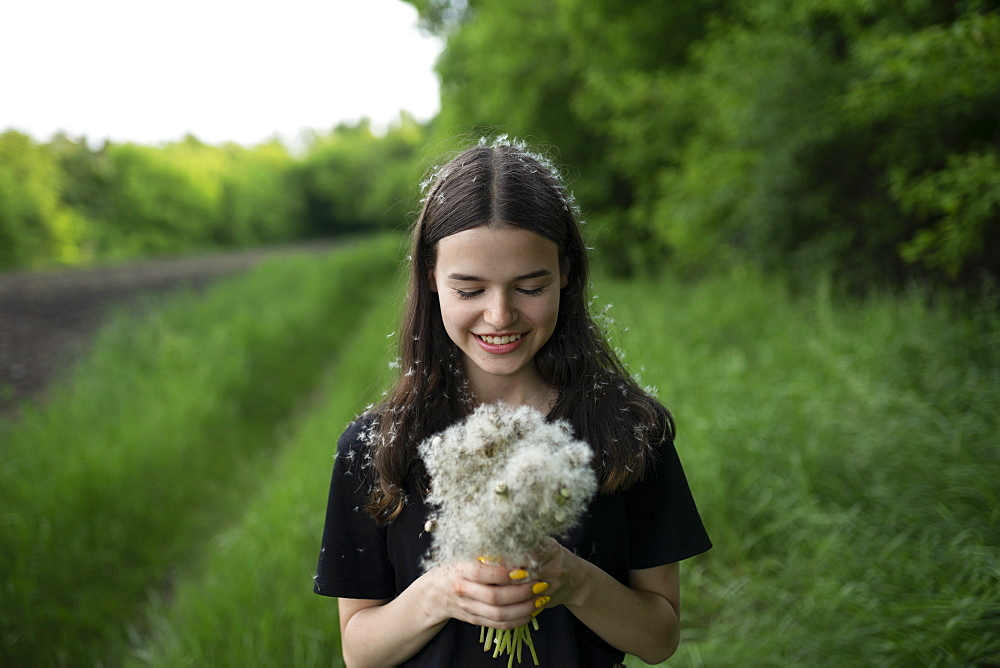 Smiling teenage girl holding dandelions in a field