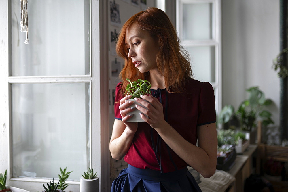 Redhead woman holding potted plant by window