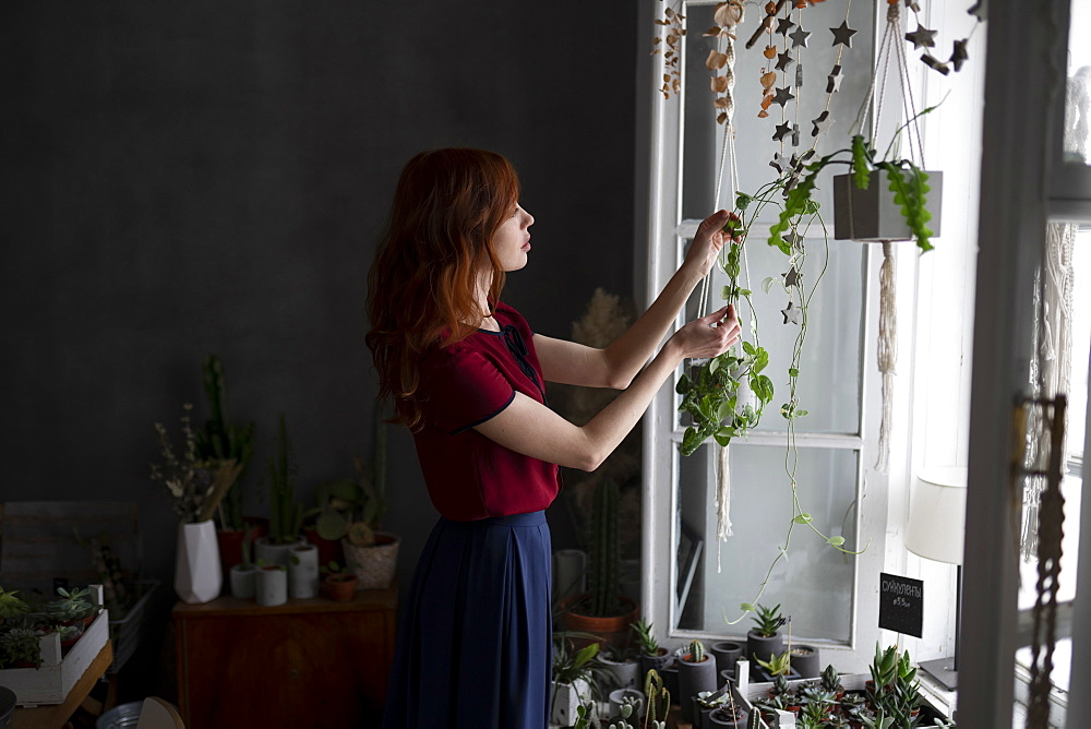 Redhead woman holding hanging plants by window