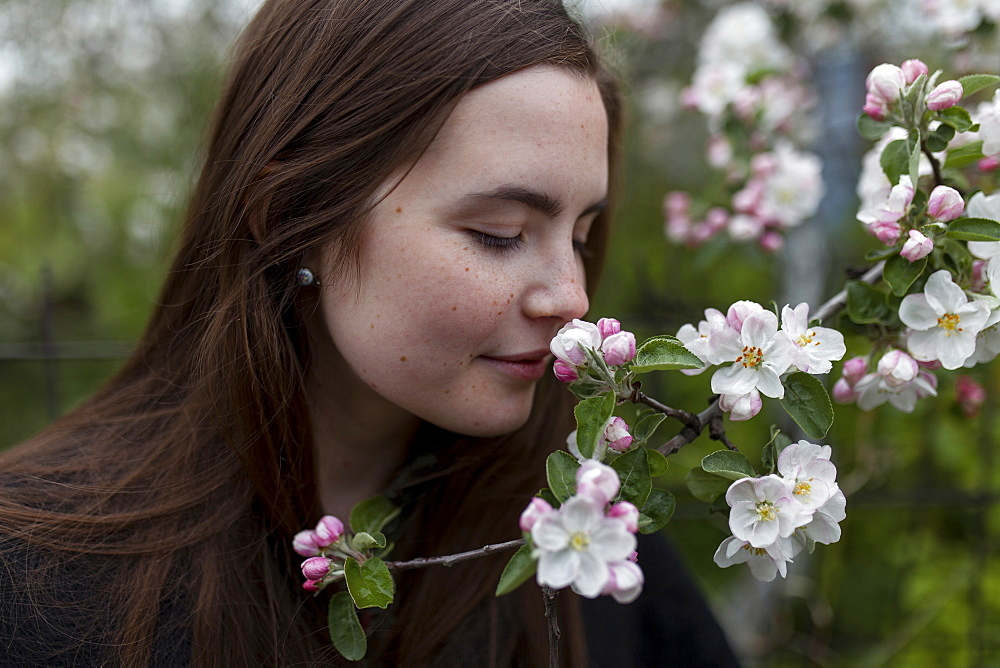 Young woman smelling white blossoms