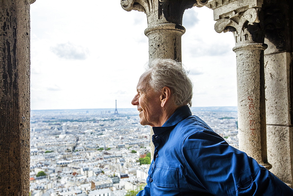 Smiling man by cityscape from Sacre Coeur in Paris, France