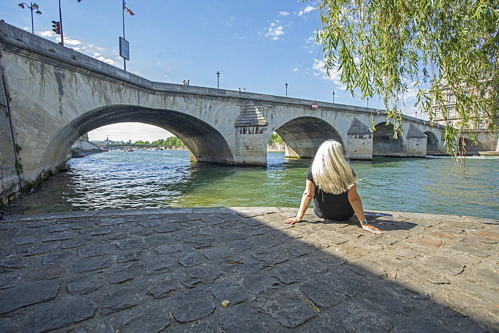 Woman sitting by bridge over Seine River in Paris, France