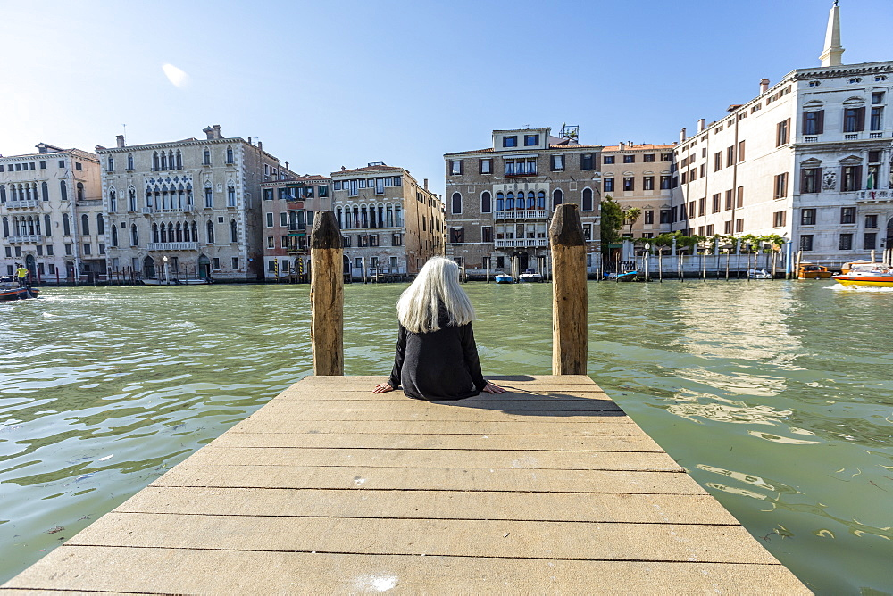 Woman sitting on jetty on Grand Canal in Venice, Italy