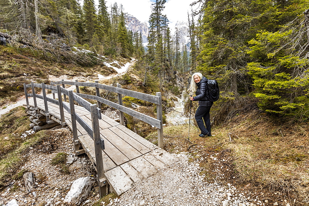 Woman hiking by footbridge on Giau Pass in Belluno, Passo Giau, Belluno, Italy