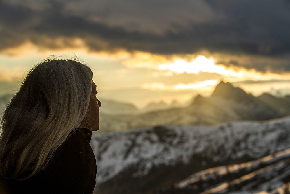 Mature woman by mountains at sunset in Dolomites, Passo Giau, Belluno, Italy
