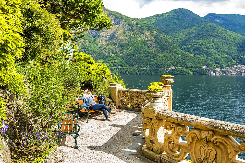 Woman on park bench at Villa del Balbianello by Lake Como, Italy