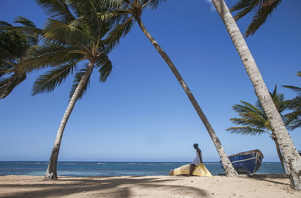 Woman sitting on boat under palm trees on beach in Las Terrenas, Dominican Republic