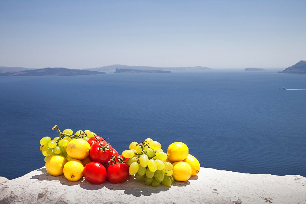 Fruit on white wall by sea, Santorini, Cyclades Islands, Greece