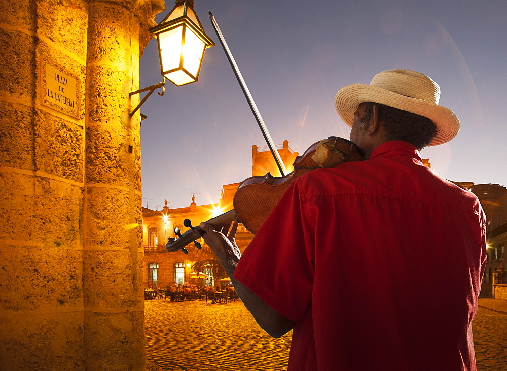 Senior man playing violin at night in Plaza de la Catedral, Havana, Cuba