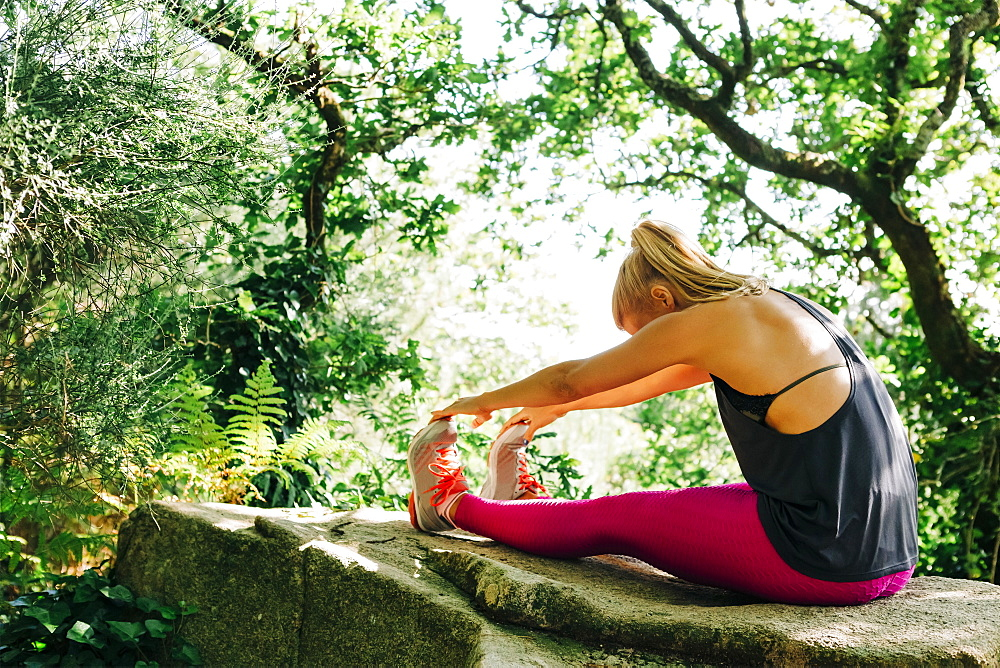 Woman stretching on rock in forest