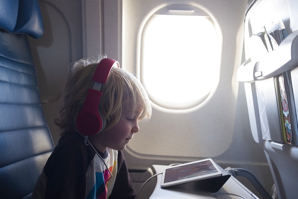Boy watching digital tablet on airplane