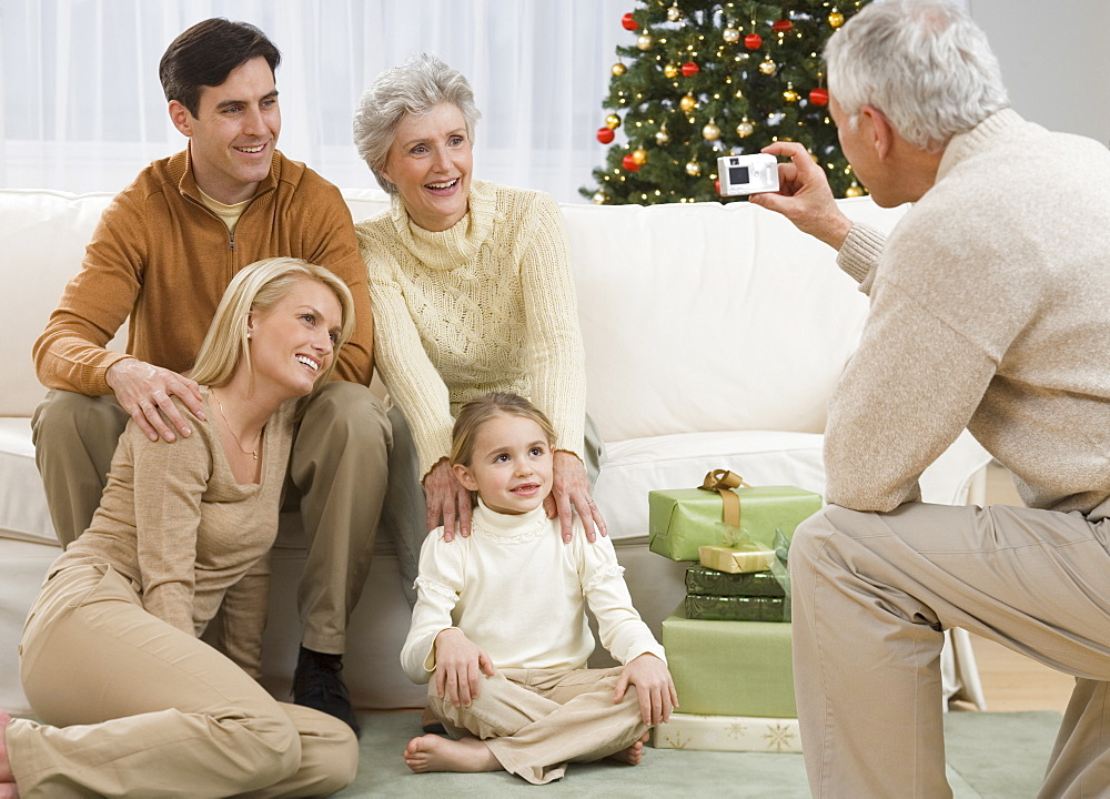 Grandfather taking photograph of family on Christmas
