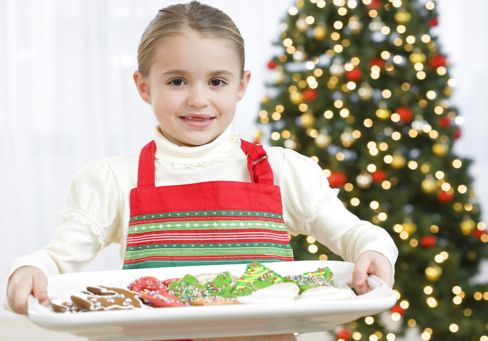 Girl carrying tray of Christmas cookies