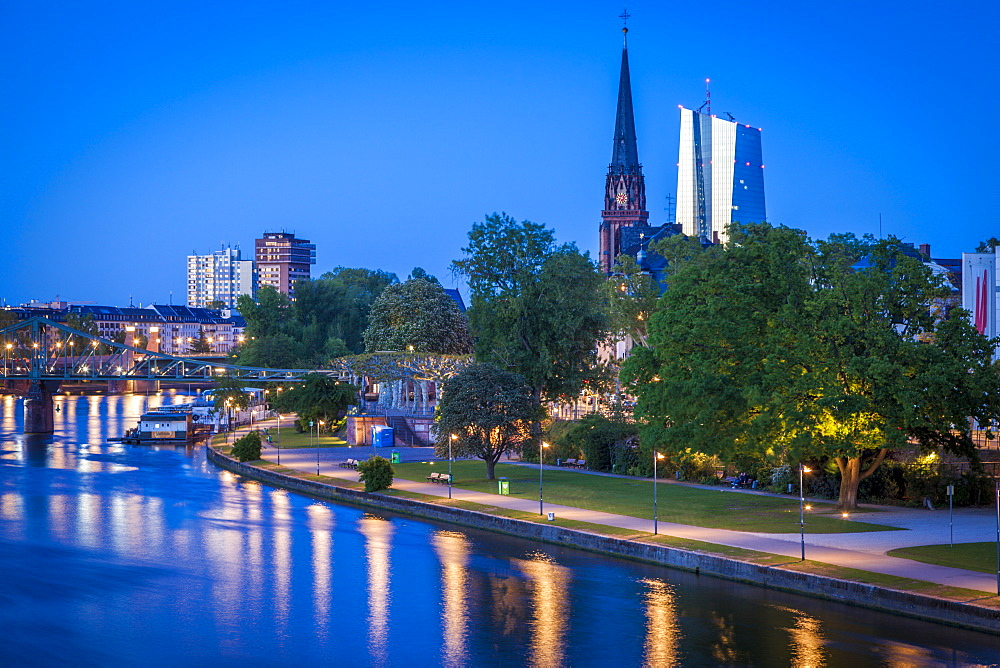 Church and office towers by river at sunset in Frankfurt, Germany