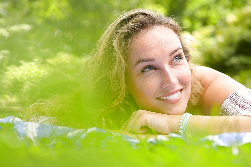 Smiling young woman lying in garden