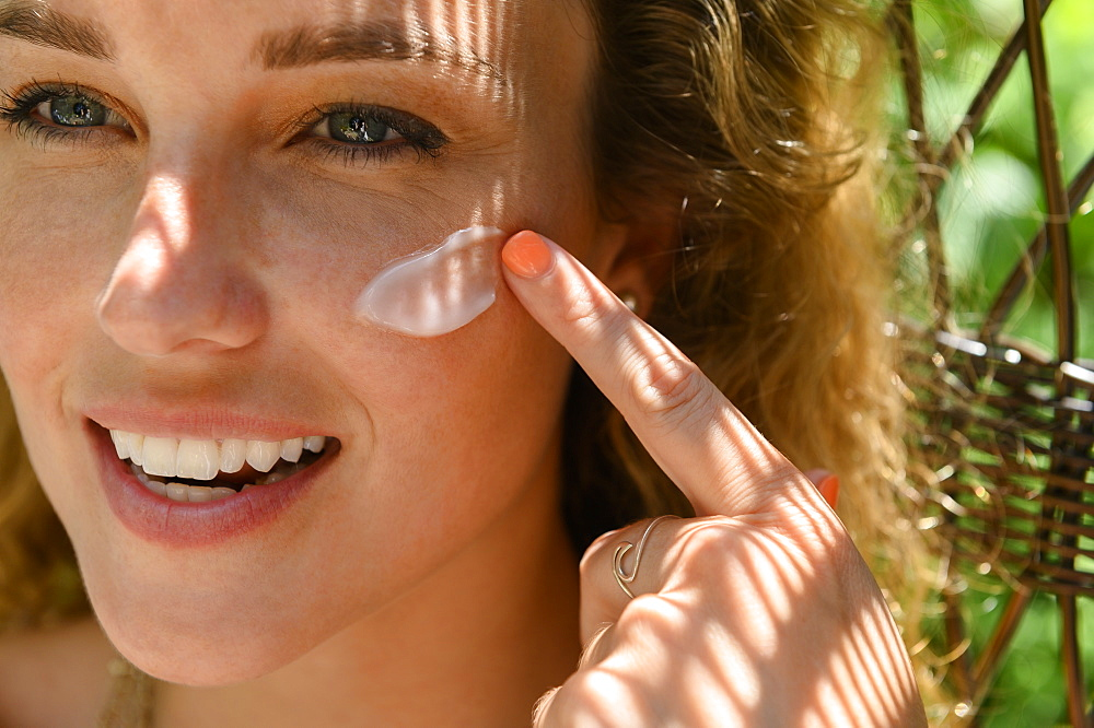 Young woman applying sun cream