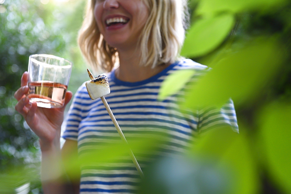 Smiling woman holding glass of wine and toasted marshmallow