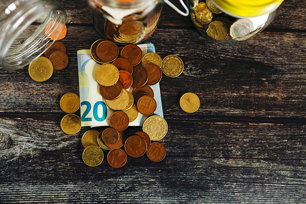 Euro coins on twenty Euro note by glass jars