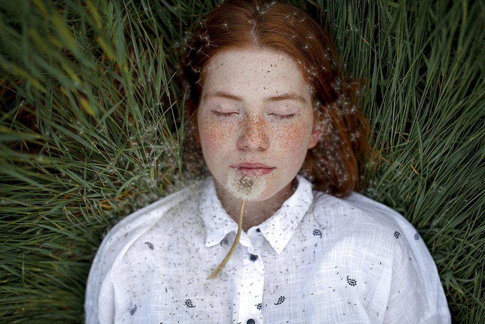 Teenage girl lying down with dandelion seedhead