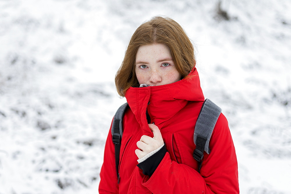 Teenage girl wearing red coat in snow