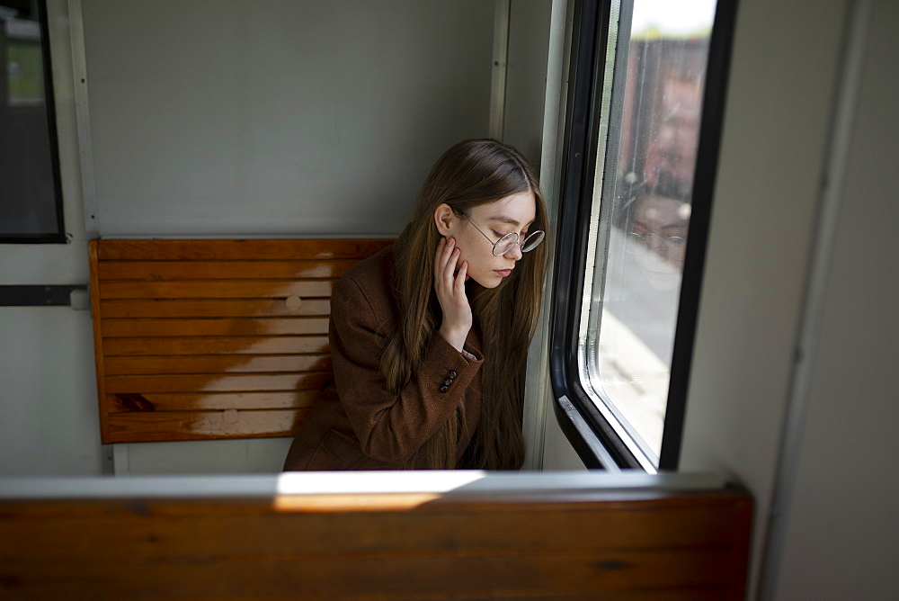 Young woman wearing glasses by window on train