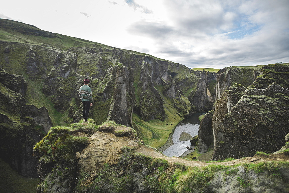 Young man standing on cliff above canyon in Kirkjubµjarklaustur, Iceland