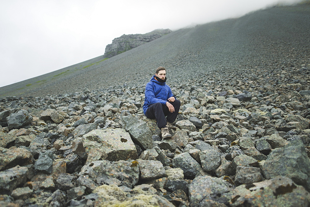 Young man sitting on rock hill in Kirkjubµjarklaustur, Iceland