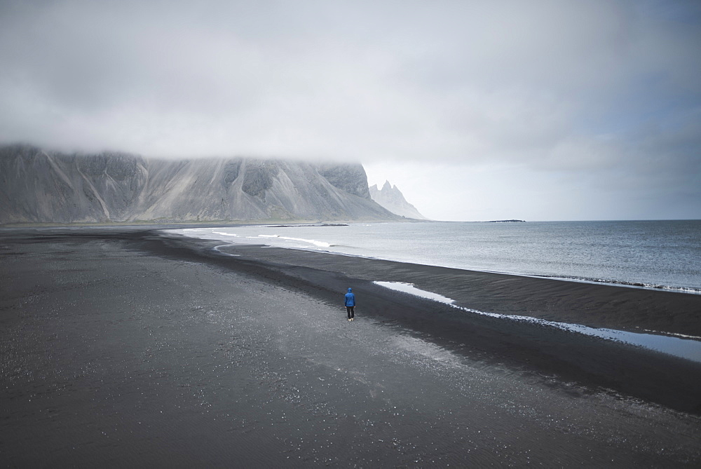 Man walking on black sand beach in Kirkjubµjarklaustur, Iceland