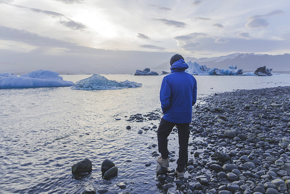 Man wearing blue coat by Jokulsarlon glacial lake in Iceland