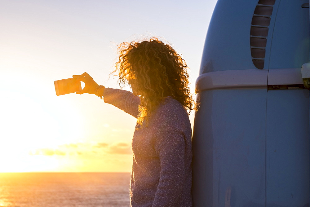 Woman taking selfie by camper van at sunset