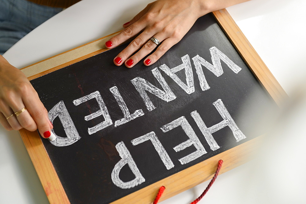 Woman writing 'Help Wanted' on chalkboard