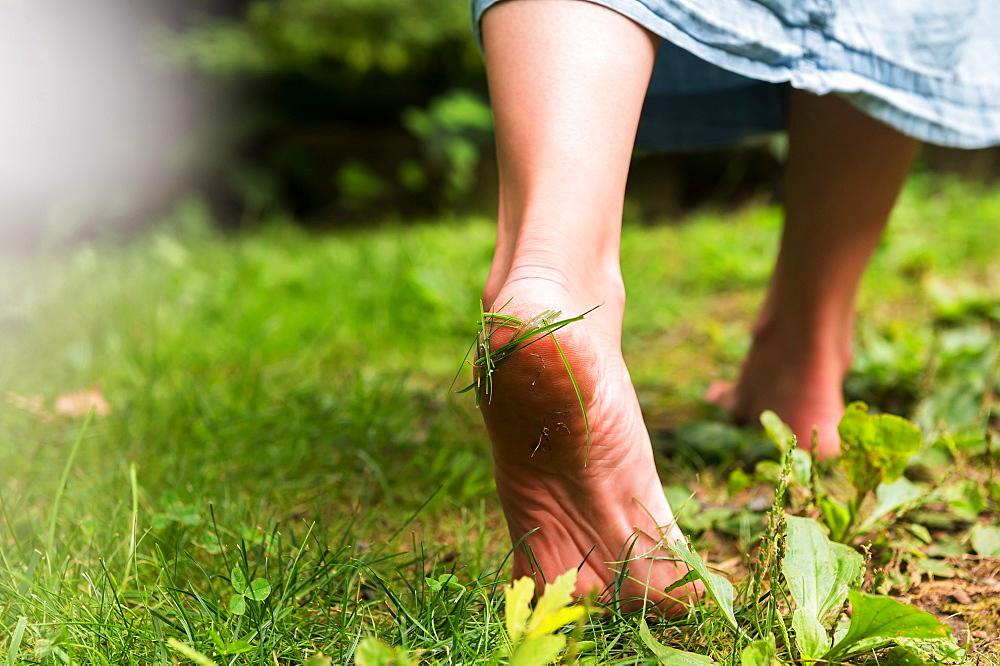 Woman walking barefoot on grass