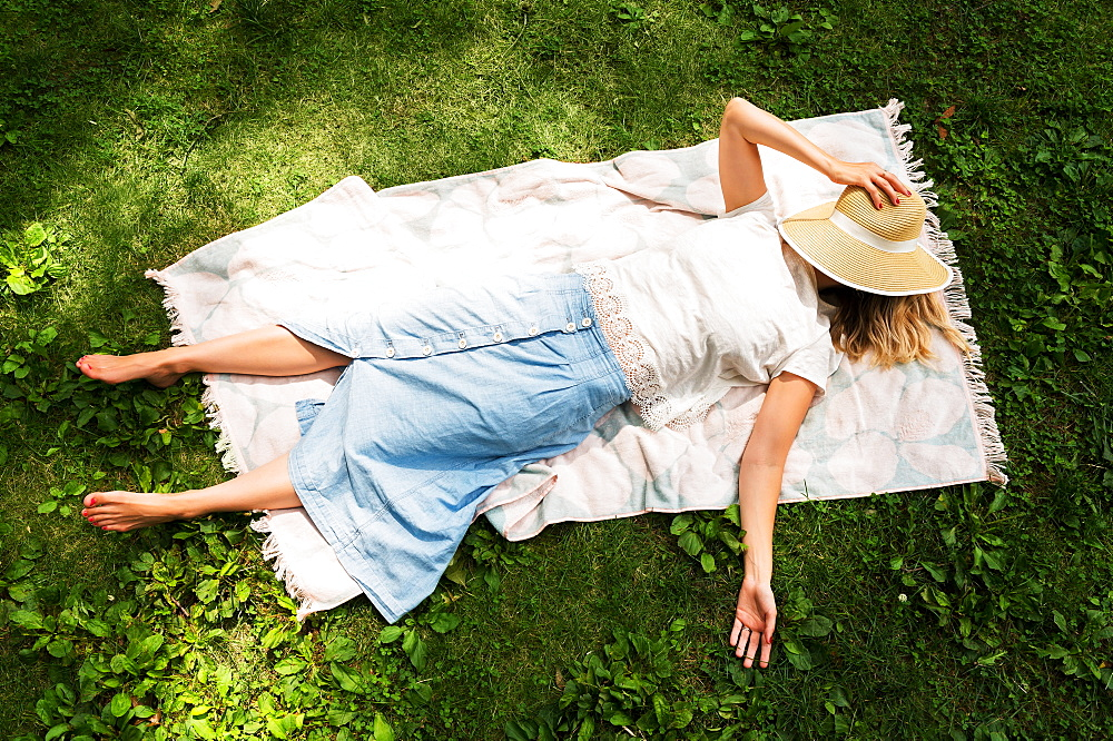 Woman lying on blanket in park