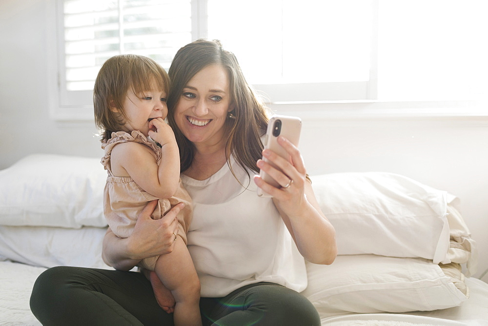 Mother and daughter taking selfie on bed - 1178-27846