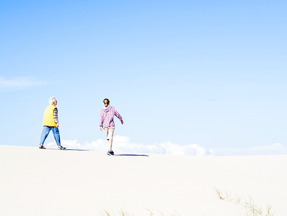 Mother and daughter walking on sand dune in Hawke's Nest, New South Wales, Australia