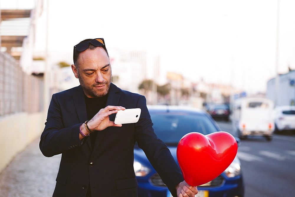 Man photographing red heart shaped balloon
