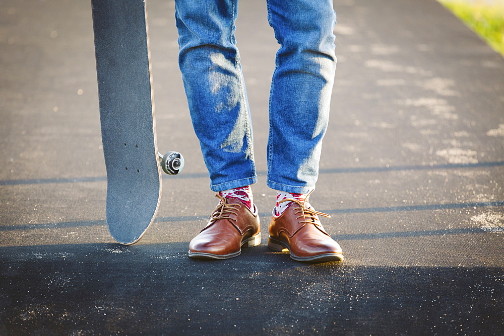 Feet of man with skateboard on footpath