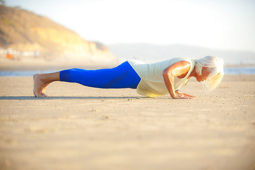 Mature woman doing push-ups on beach