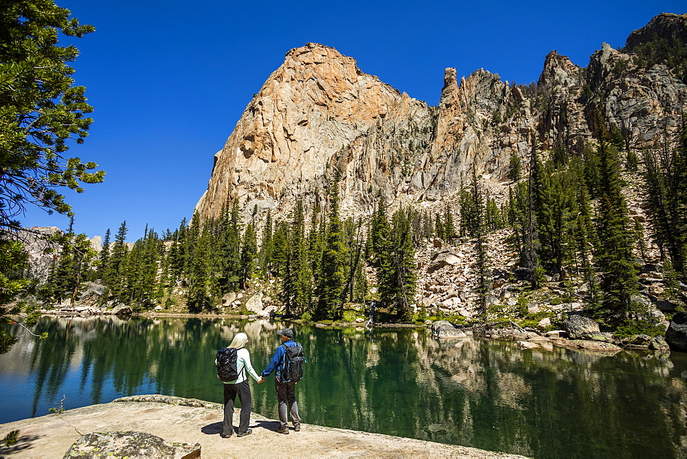 Couple holding hands by river in Sawtooth Mountains in Stanley, Idaho, USA