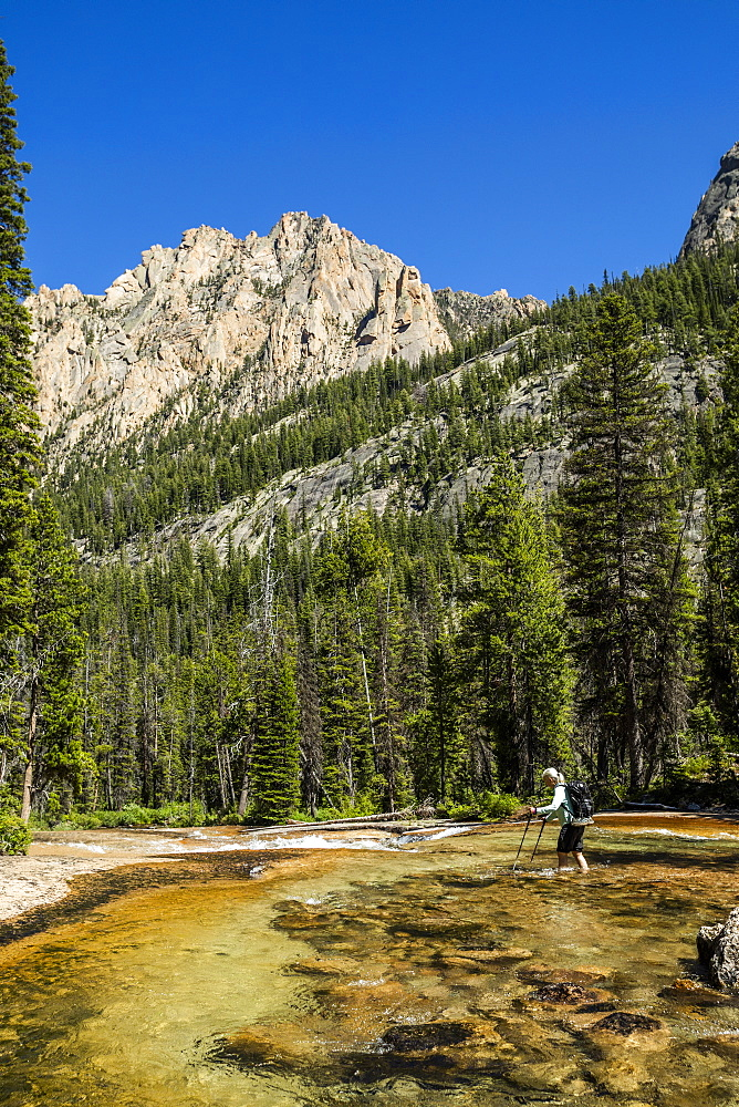 Woman wading through river by Sawtooth Mountains in Stanley, Idaho, USA - 1178-27894