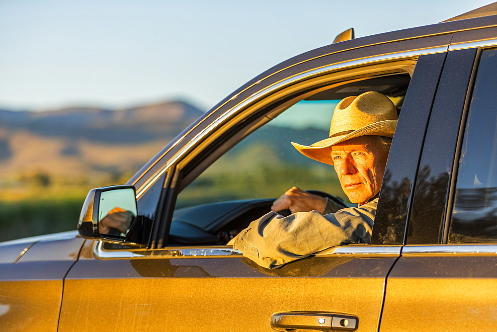 Farmer wearing cowboy hat driving SUV