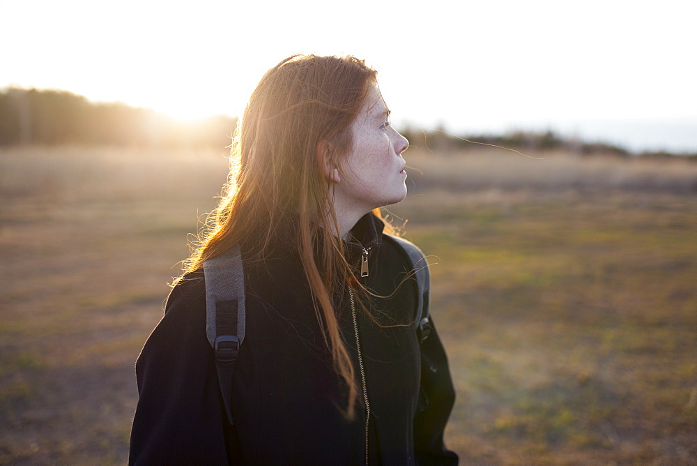 Teenage girl wearing backpack in field at sunset