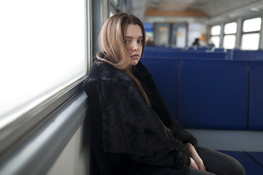 Young woman wearing black fur coat on train