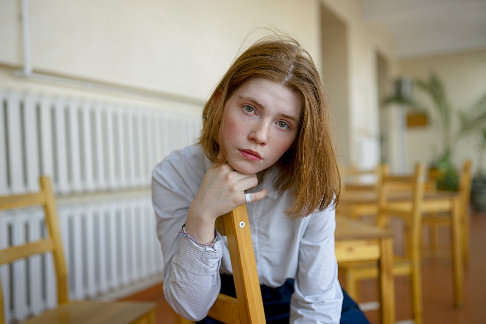 Young woman leaning on wooden chair